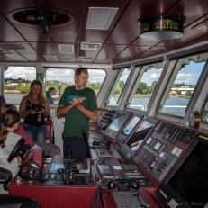 Crewman talking with visitors on the bridge.